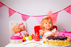 Cute little girl with sweets and dolls at birthday party Royalty Free Stock Photo