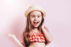 Cute little girl in swim suit and straw hat talking on telephone royalty free stock image