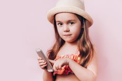 Cute little girl in swim suit and straw hat talking on telephone royalty free stock photo