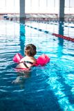 Cute little girl swimming in the pool. stock photography
