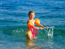 Cute little girl swimming in the sea with water wing. Childhood concept Stock Image