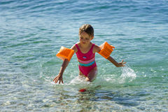 Cute little girl swimming in the sea with water wing. Childhood concept Stock Images