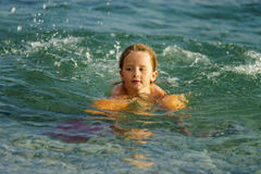 Cute little girl swimming in the sea with water wing. Childhood concept Stock Photography