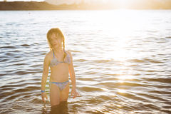 Cute little girl in swimsuit standing in the sea water on the be Stock Photos