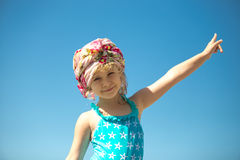 Cute little girl in swimwear against blue sky Royalty Free Stock Images