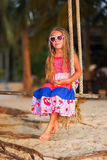 Cute little girl on a swing. A child plays outdoors in summer. Royalty Free Stock Images
