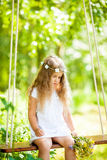 Cute little girl on the swing. With flowers Royalty Free Stock Photos