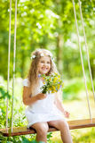 Cute little girl on the swing. Cute funny little girl on the swing with flowers Stock Photos