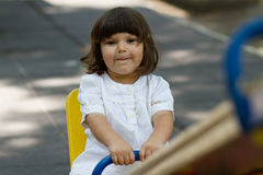 Cute little girl on swing in the playground Royalty Free Stock Photo
