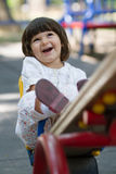 Cute little girl on swing in the playground Stock Image