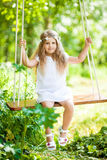 Cute little girl on the swing. Cute little girl on the wooden swing Stock Image