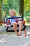 Cute little girl swinging at playground. Happy little child, smiling blonde toddler girl in casual outfit having fun on a swing enjoying a warm sunny summer day Stock Photo