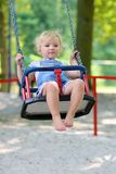 Cute little girl swinging at playground. Happy little child, smiling blonde toddler girl in casual outfit having fun on a swing enjoying a warm sunny summer day Royalty Free Stock Photo