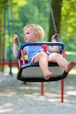 Cute little girl swinging at playground. Happy little child, smiling blonde toddler girl in casual outfit having fun on a swing enjoying a warm sunny summer day Stock Images