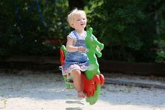 Cute little girl swinging at playground. Happy little child, smiling blonde toddler girl in casual outfit having fun on a swing enjoying a warm sunny summer day Royalty Free Stock Photos