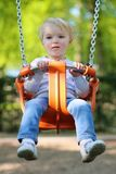 Cute little girl swinging at playground. Happy little child, smiling blonde toddler girl in casual outfit having fun on a swing enjoying a warm sunny summer day Stock Photography