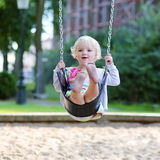 Cute little girl swinging at playground. Happy little child, smiling blonde toddler girl in casual outfit having fun on a swing enjoying a warm sunny summer day Royalty Free Stock Image