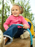 Cute little girl is swinging on see-saw. Happy little girl is swinging on see-saw Royalty Free Stock Photos