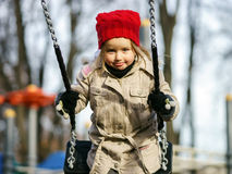 Cute little girl swinging on seesaw. On children payground Royalty Free Stock Image