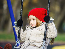 Cute little girl swinging on seesaw. On children payground Royalty Free Stock Photos