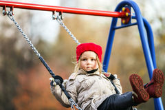 Cute little girl swinging on seesaw. On children payground Royalty Free Stock Photo