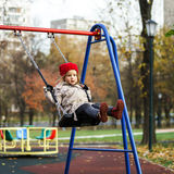 Cute little girl swinging on seesaw. On children payground Stock Image
