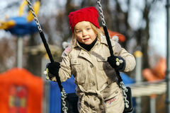 Cute little girl swinging on seesaw. On children payground Stock Photo