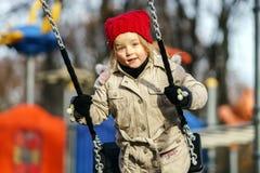 Cute little girl swinging on seesaw Stock Photo