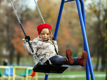 Cute little girl swinging on seesaw. On children payground Stock Photography