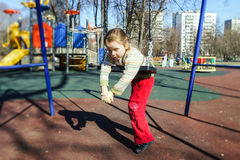 Cute little girl swinging seesaw on children playground Stock Images