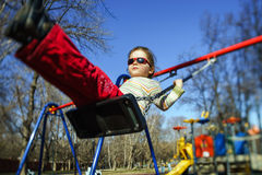 Cute little girl swinging seesaw on children playground. Cute little girl swinging on seesaw on children playground Stock Photography