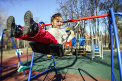 Cute little girl swinging seesaw on children playground. Cute little girl swinging on seesaw on children playground Stock Image