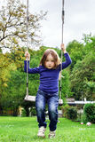 Cute little girl swinging on seesaw. To the sky Stock Photo