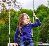 Cute little girl swinging on seesaw. To the sky Royalty Free Stock Images