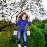Cute little girl swinging on seesaw. To the sky Stock Images