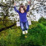 Cute little girl swinging on seesaw. To the sky Royalty Free Stock Photography