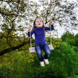 Cute little girl swinging on seesaw. To the sky Royalty Free Stock Photo