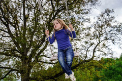 Cute little girl swinging on seesaw Stock Images
