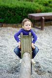 Cute little girl swinging on seesaw. To the sky Royalty Free Stock Image