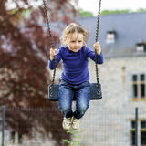 Cute little girl swinging on seesaw. To the sky Stock Photos