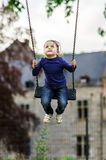 Cute little girl swinging on seesaw. To the sky Royalty Free Stock Photos