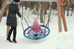 Cute little girl swinging on a swing on the playground in winter. Winter family entertainment concept Stock Photography