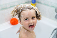 Cute little girl taking a bath with foam Stock Images