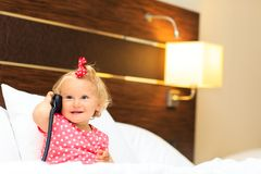 Cute little girl taking on the phone in hotel room Stock Images