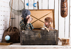 Cute little girl taking photo of another little girl in wooden chest Royalty Free Stock Image