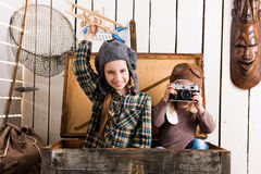 Cute little girl taking photo of another little girl in wooden chest Stock Photo