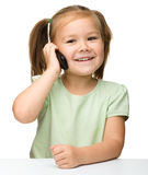 Cute little girl is talking on cell phone Stock Images