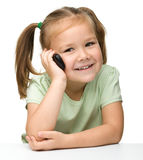 Cute little girl is talking on cell phone. While sitting at table, isolated over white Stock Photography