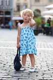 Cute little girl talking on mobile phone in the city Royalty Free Stock Image