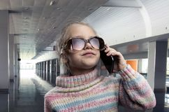 Cute little girl talks on phone Stock Image